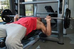 Bench Press At Gym. Young Men In Gym Exercising On The BenchPress