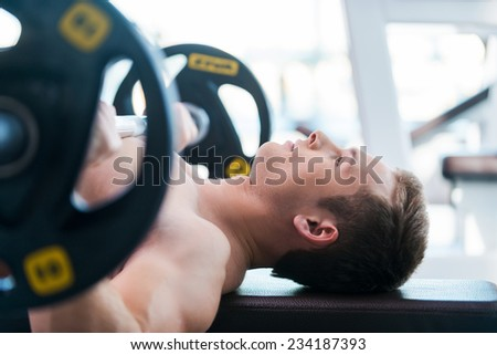 Bench press. Confident young muscular man working out on bench press