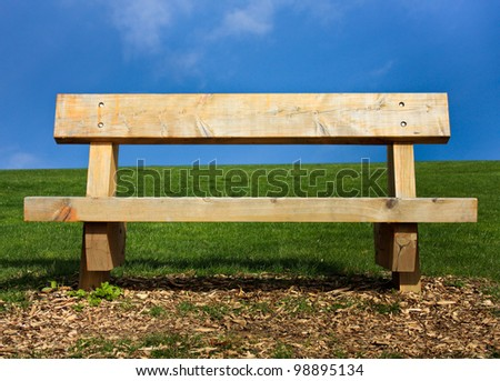 Bench situated on wood chips and grass against a blue sky