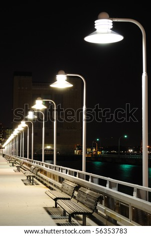 Benches and lamp posts on a pier at night.