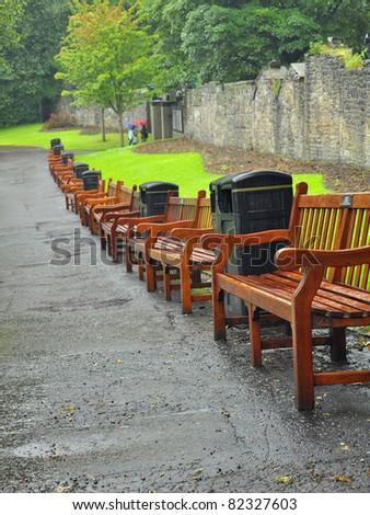 Benches in Princes Street Gardens, rainy weather in Edinburgh, Scotland (vertical).