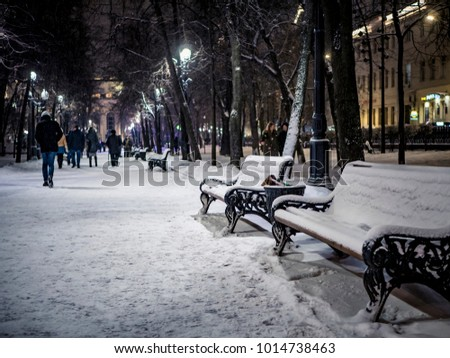 benches in the city park at winter snowy night, alley with people walking by