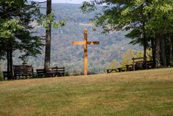 Benches surrounding wooden cross, a place to sit and pray
