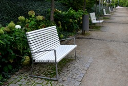 benches with metallic shiny stainless steel construction, armrests, white wood paneling in public parks. under a bench of granite cobblestone tiles. park lawn with white flowering shrubs. harmony