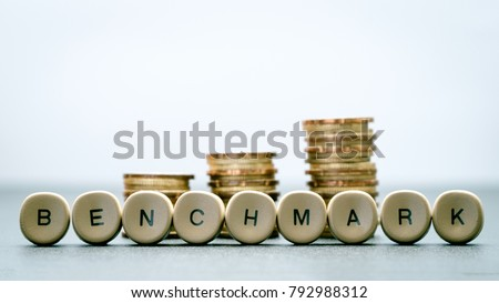BENCHMARK letter block and stack coins, business concept. #792988312