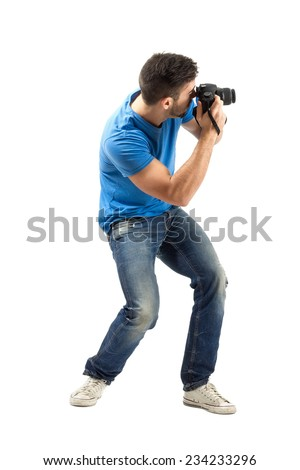 Bend young man taking photo with digital camera side view Full body length portrait isolated over white background