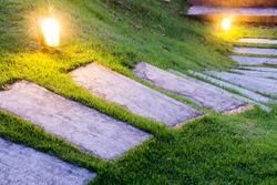 Bending garden stone path at night with glowing light from garden outdoor light