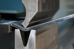 Bending sheet metal with a hydraulic machine at the factory. Closeup.