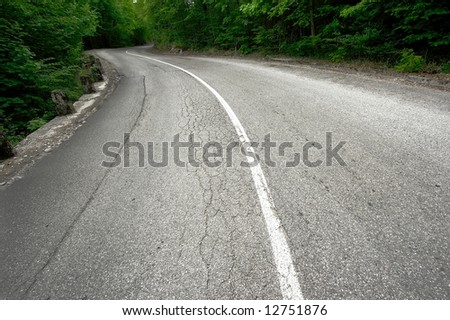 Bendy mountain road going through a forest