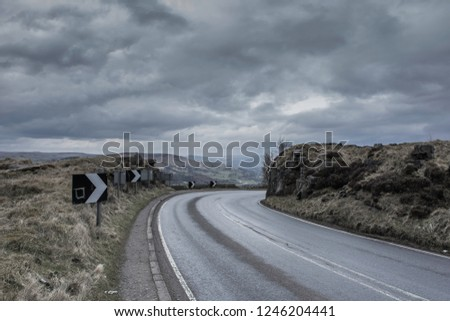 Bendy rural road wet after rain with rocks on side and scenic view on beautiful mountain valley, on Derbyshire countryside, UK.Travel photography.Transportation in rough terrain.Moody sky over passage