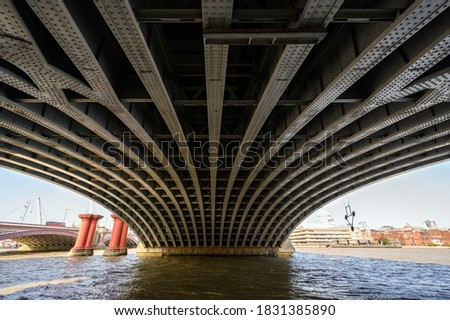 Beneath Blackfriars Railway Bridge in London, UK. The steel beams hold the structure in place with the Blackfriars station above. Also Blackfriars Road Bridge, St Pauls Cathedral and River Thames.