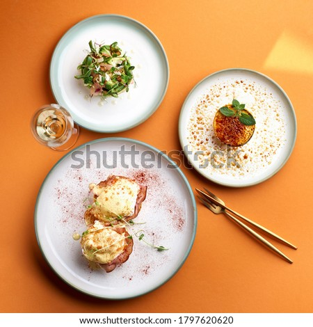 Benedict eggs - poached eggs and a delicious avocado salad, dessert cr me brulee in orange background Photo stock ©