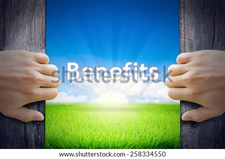 Benefits. Hand opening an old wooden door and found Benefits word floating over green field and bright blue Sky Sunrise.