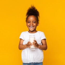 Benefits of dairy products drinking. Cute afro girl enjoying glass of milk, orange studio background