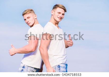 Benefits of having twin brother. Friendship of brothers. Benefits and drawbacks of having identical twin brother. Men twins brothers muscular guys in white shirts sky background. Brotherhood concept.