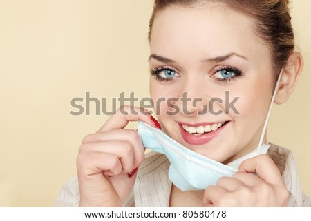 benevolent woman medical worker removes the mask - stock photo