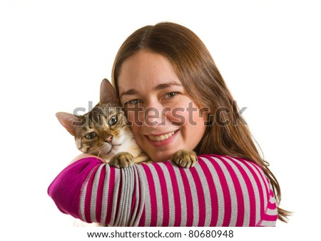 Bengal cat sits on shoulder of young woman and stares at camera in isolated studio shot showing love between pet and owner