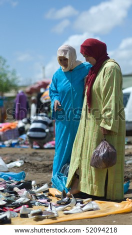 BENI MELLAL, MOROCCO - APRIL 16: Two women looking for shoes on a souk (market) April 16 2010 in Beni Mellal near Marrakesch, Morocco. - stock photo