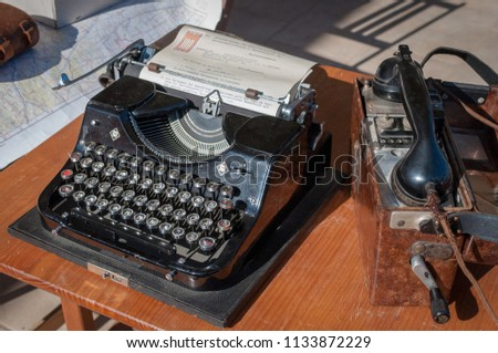 BENICASIM - SEPTEMBER 2018: Telephone and typewriter of the 1940 World War in a historical recreation. #1133872229