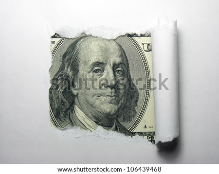 Benjamin Franklin macro peeking through torn white paper.