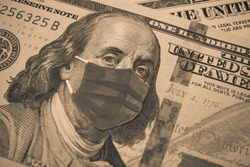 Benjamin Franklin president wear face mask on US dollar bill banknote background. Global novel coronavirus (Covid-19) outbreak effect to USA, world economy, financial crisis, investment, stock market.