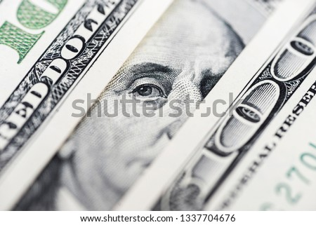 Benjamin Franklin's eyes from a hundred-dollar bill. The face of Benjamin Franklin on the hundred dollar banknote, backgrounds, close-up. 100 dollar bill with only eyes of Benjamin Franklin