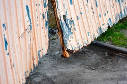 Bent corrugated door of the gate with the rails is close