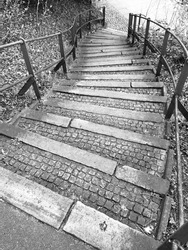 Bent curved historic stairs looking downstairs with metal handrail, cobblestone pattern and structure on a black and white upright picture