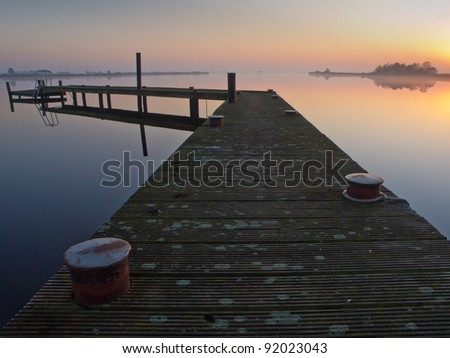 Bent jetty with mooring post during sunset over lake
