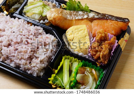 Bento / Japanese lunch box with grilled salmon and side dish
