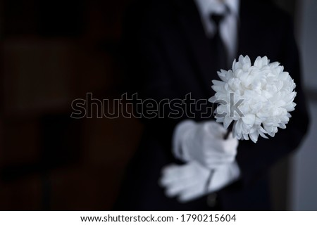 Bereaved holding flowers at funeral