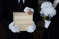 Bereaved holding urn with flowers
