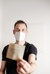 Berechtigungsschein. young man with FFP2 mask holds a blurred certificate of authorization in his hand.