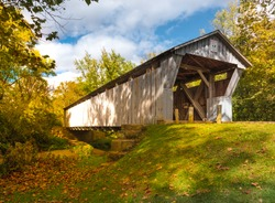 Bergstresser Dietz Covered Bridge in Canal Winchester, Ohio spanning Walnut Creek with blue sky and autumn trees