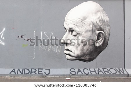 BERLIN - AUGUST 22: Famous graffito of academician Andrei Sakharov on Berlin Wall at East Side Gallery August 22, 2012 in Berlin - stock photo