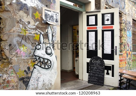 BERLIN - AUGUST 01: Typical grunge art court with graffiti on August 01, 2012 in Berlin. Cafe entrance in graffiti court in Scheunenviertel, stylish district in Berlin.