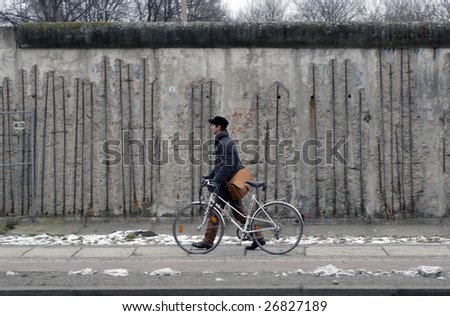 BERLIN - FEBRUARY 13: A man walks his bicycle past a section of the Berlin Wall at Bernauer Strasse on February 13, 2009 in Berlin. The main Wall separating East and West Germany came down in 1989.