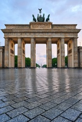 berlin germany, deserted brandenburg gate with reflections on the wet asphalt and with clouds at the sunset. special perspective as close-up from the ground,