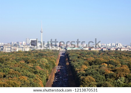 Berlin, Germany - October 13th 2018: Aerial view of Berlin skyline with Television Tower and Brandenburg Gate from the Victory Column on Tiergarten. A demonstration taken place and people marching.