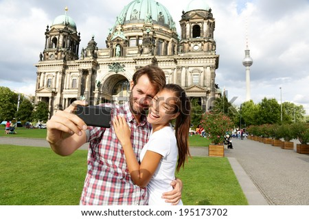 Berlin Germany travel couple selfie self portrait. Happy tourists people in front of Berlin Cathedral / Berliner Dom with Fernsehturm / Berlin TV Tower in the background. Asian woman, Caucasian man.