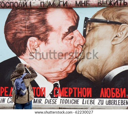BERLIN - SEPTEMBER 26: Tourist takes photos with the famous kiss from the Berlin Wall containing now new designs Sept 26, 2010 in Berlin.