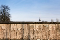 Berlin Wall original weathered section damaged with exposed iron bars partly covering the TV tower (Berliner Fernsehturm) far in the horizon.