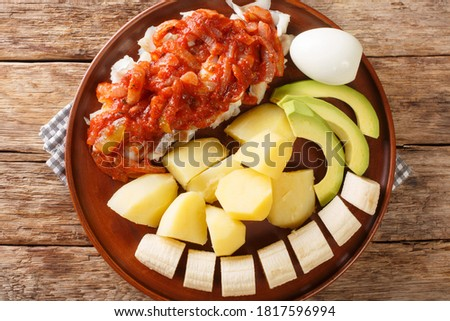 Bermuda codfish breakfast with onion tomato sauce, boiled potatoes, eggs, banana and avocado close-up in a plate on the table. horizontal top view from above Stock photo ©