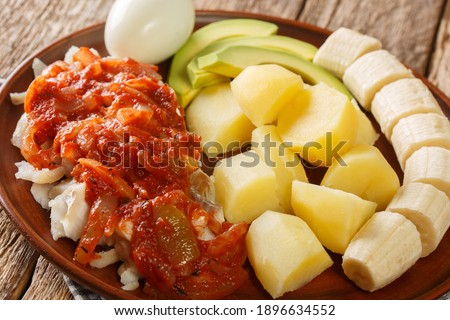 Bermuda codfish breakfast with onion tomato sauce, boiled potatoes, eggs, banana and avocado close-up in a plate on the table. Stock photo ©