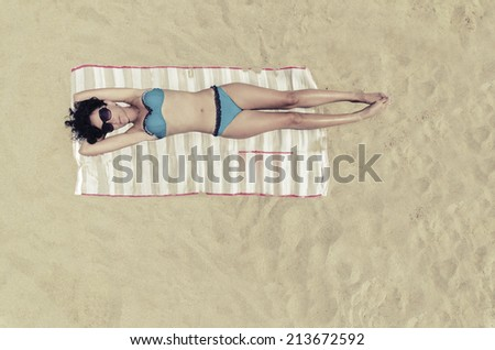Bermuda Sunbathing, Beautiful brunette girl is sunbathing on an empty beach, aerial view from top. VINTAGE