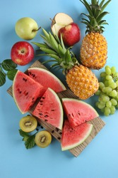 Berries and fruit. Watermelon, pineapple, kiwi, apples and green grapes on a bright blue background. Flatlay, top view. Background image, copy space