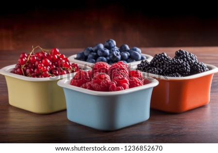 Berries arrangement front view in four ceramic jars on rustic black table and dark background. Blueberry, raspberry, red currant, strawberry, blackberry