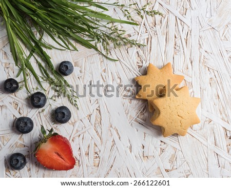 Berries, cookies and grass on wooden table