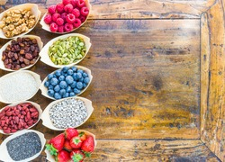 Berries, fruits, nuts, seeds top view on rustic wood background.Healthy breakfast, superfood concept, text space.