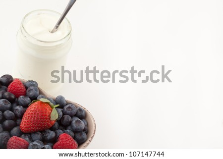 Berries in a heart shaped bowl with white yogurt against a white background